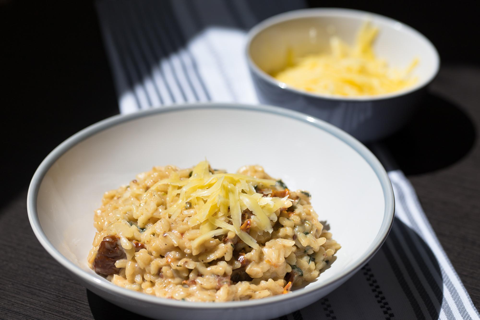 Talianske krémové rizoto so sušenými paradajkami a listami špenátu.